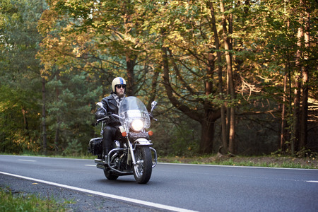 Handsome bearded biker in sunglasses, helmet and black leather clothing riding cruiser motorcycle along asphalt road winding among tall green trees on sunny summer evening.