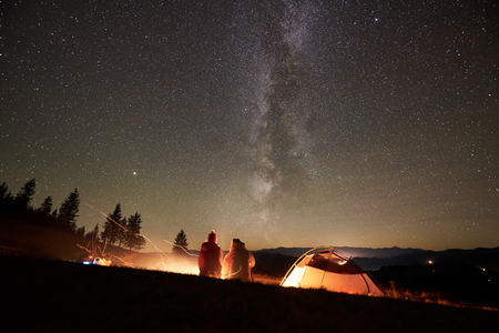Night summer camping in the mountains. Back view of happy couple hikers sitting together beside campfire and glowing tourist tent under beautiful night starry sky full of stars and Milky way. Reklamní fotografie
