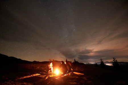 Three tourists travelers, two men and young woman sitting on big logs by burning campfire on grassy mountain valley with small spruce trees enjoying beautiful camping night under starry cloudy sky. Stockfoto