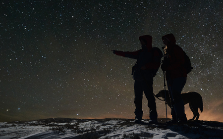Adult experienced skier with dog showing discovered way from mountain peak to another tourist skier in night ski-tour. Silhouettes in mountains. Incredible starry sky before sunrise on background. Stock Photo