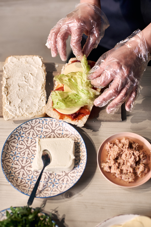 Chefs hands in gloves putting layers of ingredients on big appetizing sandwich. Decorating with green salad leaves. Components of dish in plates on light wooden background. Close up top view.