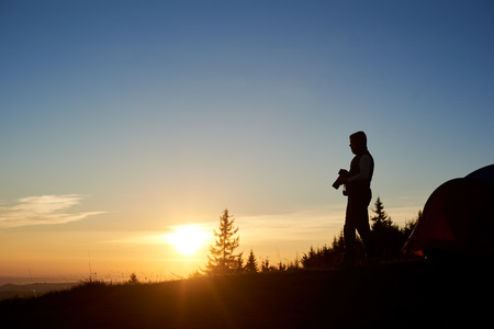 Silhouette of happe man photographer with photo camera standing near tourist tent on the top of mountain in the evening at sunset. On background beautiful view of setting sun and blue sky.