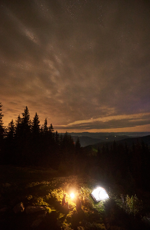 Vertical shot, top view of night summer camping in the mountains. Young couple hikers sitting together beside campfire and illuminated tourist tent under beautiful night cloudy sky with stars.