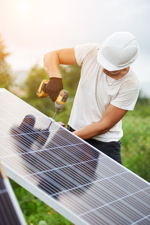 Professional worker in helmet and protective gloves connecting solar photo voltaic panel to platform using electrical screwdriver on bright sunny sky and green trees background. Reklamní fotografie