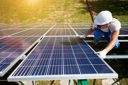 Innovative solar panels installing by young worker wearing blue uniform and protective helmet. Innovative solution for electricity saving, using renewable energy of sun. High-tech exterior. Stok Fotoğraf