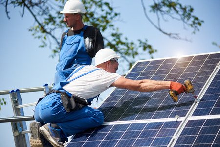 Two workers mounting heavy solar photo voltaic panel on tall steel platform using screwdriver on blue sky background. Exterior stand-alone solar panel system installation, dangerous job concept. Reklamní fotografie