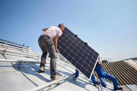 Trabajadores varones instalando un sistema de paneles solares fotovoltaicos independientes. Los electricistas levantan el módulo solar azul en el techo de la casa moderna. Concepto renovable de recursos sostenibles de energía alternativa.