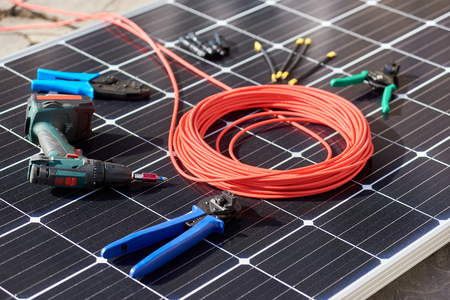 Close-up view of different details and instruments for mounting and connecting solar photovoltaic system. Objects laying on blue solar panel. Alternative energy resources renewable ecology concept. Stock Photo