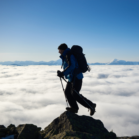 Tourist man with backpack and hiker sticks standing on top of big rock on background of bright blue sky, foggy valley filled with white clouds and distant mountain tops covered with first snow.