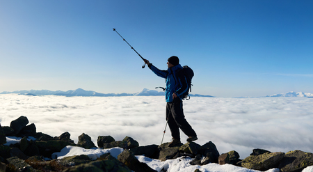 Tourist hiker with backpack standing on huge rocks on the top of mountain pointing with trekking pole at blue sky on background of foggy valley filled with white clouds and distant mountain tops.