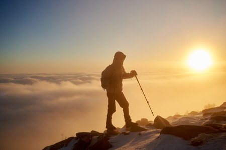 Silhouette of tourist hiker with backpack and hiking sticks walking on rocky mountain top on copy space background of beautiful foggy valley filled with white puffy clouds at sunrise.
