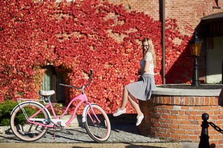 Attractive long-haired smiling blond girl in short skirt and blouse l sitting on low brick wall at pink lady bicycle on bright warm sunny day on background of house overgrown with beautiful red ivy. Banco de Imagens