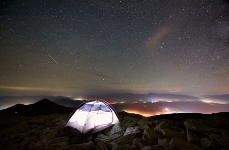 Tourist summer camping at night on the top of rocky mountain. Glowing tent under incredibly beautiful night sky full of stars. On background amazing starry sky, mountains and luminous villages