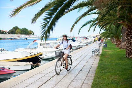 Attractive woman in sunglasses with backpack riding bicycle along stony sidewalk with iron bench and palm trees by long row of tied cruise boats. Tourism, active lifestyle and vacations concept.