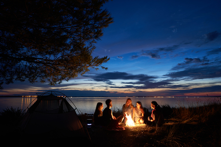 Camping d'été de nuit au bord du lac. Groupe de cinq jeunes touristes heureux assis dans l'herbe haute autour d'un feu de camp près de la tente sous un beau ciel bleu du soir. Concept de tourisme, d'amitié et de beauté de la nature Banque d'images