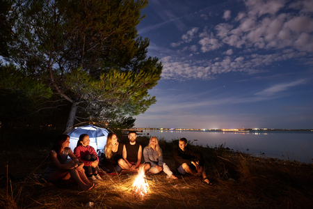 Group of six happy tourists, young men and women having a rest on sea shore under tree at campfire on tourist tent, quiet water surface and blue evening sky background. Tourism and camping concept.