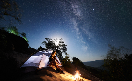 Girl traveller resting on rocky mountain top beside camp and tourist tent at summer night, warming hands by campfire under sky full of stars and Milky way. On background starry sky, boulders and trees