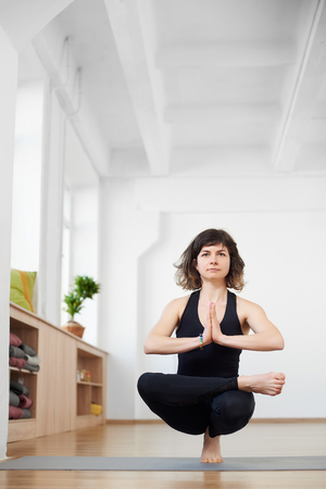 Front portrait view of young woman practicing yoga, balancing on one leg. Yogi seeking enlightenment through meditation, relaxing, performing yoga routine. Healthy body and spirit. Copy space on top