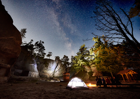 Back view of friends hikers having a rest on a bench beside camp, campfire and illuminated tourist tent at night. On background beautiful night starry sky full of stars and Milky way, mountain rocks.