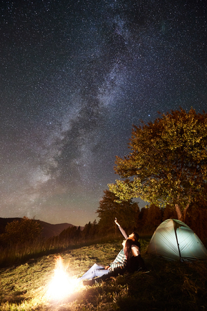 Happy couple hikers having a rest at campfire near glowing tourist tent. Man pointing at amazing night sky full of stars and Milky way. On background beautiful starry sky, mountains and big tree