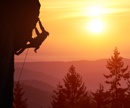 Snapshot of silhouette of male climber with copy space. Beautiful landscape with trees, mountain peaks and sunshine on orange sky on background. Over filtered. Mountain rock climbing concept.