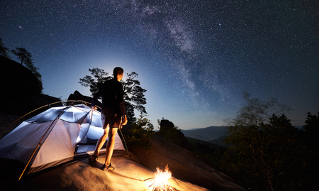 Back view of tourist man resting on rocky mountain top beside camp, bonfire and tent at summer night under night sky full of stars and Milky way. On the background starry sky, big boulders and trees