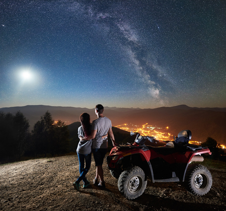 Rear view of happy young couple with atv quad motorbike on the top of mountain, boy and girl embracing, enjoying view of night sky full of stars, full moon, Milky way, luminous town on background Reklamní fotografie