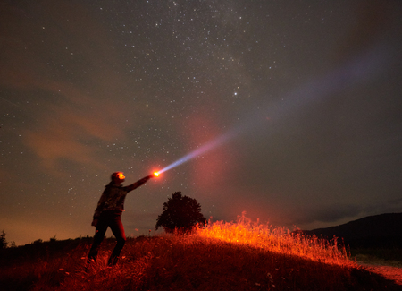 Silhouette di donna in piedi contro il cielo notturno stellato in montagna con una lampada in mano Archivio Fotografico