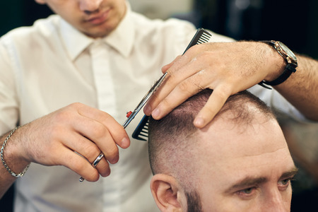 Cropped of man professional hairdresser barber making short haircut for his client in modern barbershop. Concept of traditional haircutting with scissors. Creating mens hairstyles.
