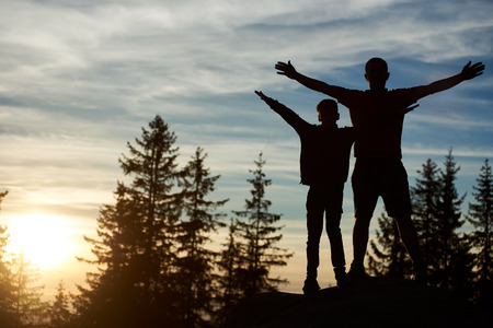 Silhouettes of happy father and son standing on the top of mountain in the evening. Young man and child hikers holding hands lifting up, enjoying beautiful sunset, trees on blurred background. Foto de archivo
