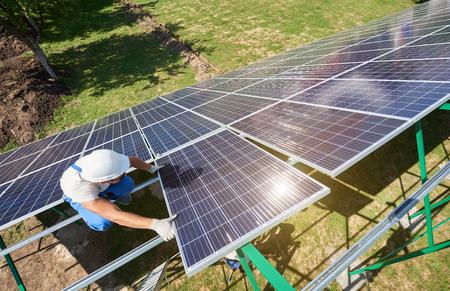 Profesjonalny pracownik instalujący panele słoneczne na zielonej metalowej konstrukcji, używający innego sprzętu, noszący kask. Innowacyjne rozwiązanie do rozwiązywania problemów energetycznych. Korzystaj z zasobów odnawialnych. Zielona energia.