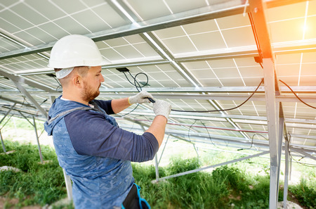 Installing and wiring of stand-alone solar photo voltaic panel system. Close-up of young electrician in hard-hat connecting electrical cables inside the solar modules. Alternative energy concept.