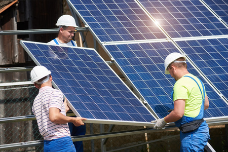 Team of three young technicians in protective helmets installing heavy solar photo voltaic panel on metal platform. Exterior solar panel system installation, efficiency and durability concept.