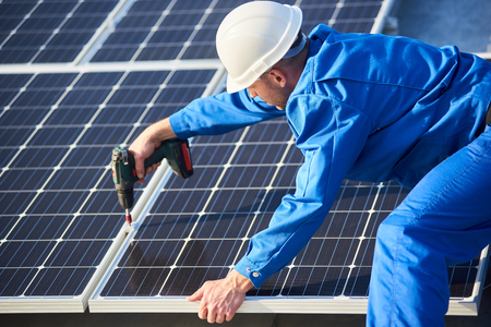 Male engineer in blue suit and protective helmet installing photovoltaic panel system using screwdriver. Professional electrician mounting solar module on roof. Alternative energy ecological concept.