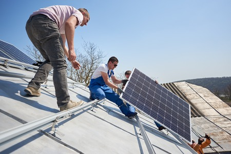 Male engineers installing solar photovoltaic panel system. Electricians lifting blue solar module on roof of modern house. Alternative energy resources renewable ecology concept.