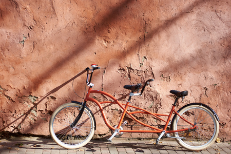 Modern comfortable orange tandem double bicycle with white wheels on paved empty sidewalk leaned against old plastered cracked red wall on bright sunny summer day. Transport and traveling concept.