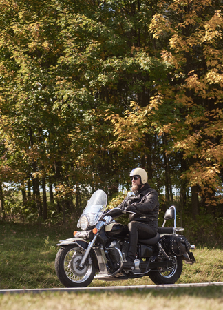 Side view of bearded motorcyclist in helmet, sunglasses and black leather clothing riding motorbike along narrow asphalt path on sunny summer day on background of tall trees and greeen grass.