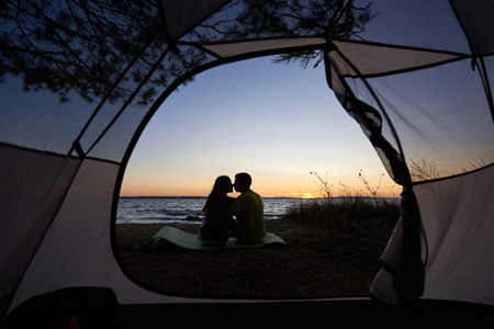 View from inside tourist tent. Dark silhouettes of young tourist romantic couple, man and woman sitting and kissing on lake shore on blue evening sky and crystal blue clear lake water background.