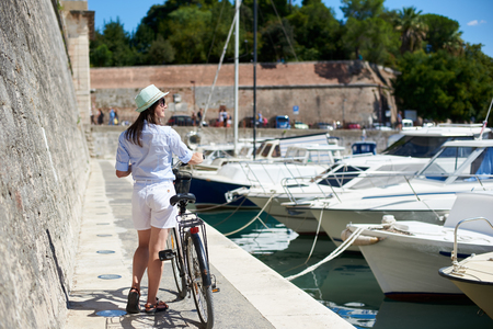 Back view of pretty smiling young woman in sunglasses and hat standing with bicycle on stone path along the sea by high stone defensive wall and long row of tied boats. Active lifestyle concept.