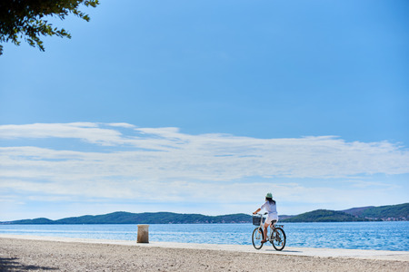 Back view of woman in white summer closing and hat riding a bicycle along stony sidewalk under clear blue sky. Sparkling sea water and mountains view on opposite shore on background. Imagens