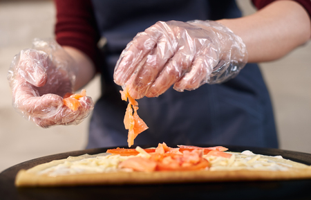 Pizza chef hands in one-time gloves keeping fish slices for preparing Italian pizza. Flat, round base, pizza dough lubricated with creamy sauce, sprinkled with grated cheese, salmon. Front focus view.