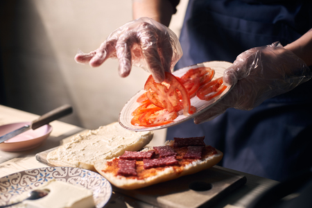 Chef mastery hands holding white plate with slices of cheese and sausage. Putting pieces of tomato on bread greased with red sauce for cooking panini. Wooden working surface. Blurred background.