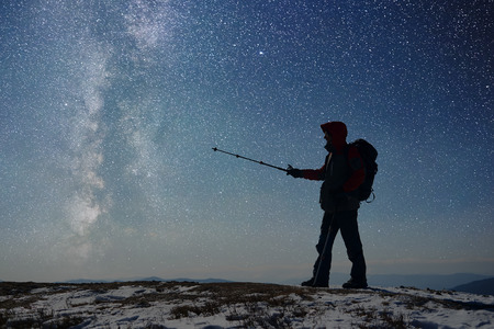 Silhouette of tourist pointing by trekking stick on Milky Way. Hiker with backpack standing on snow-covered top of mountains. Hiking in darkness. Starry sky, Milky Way on background. General side view
