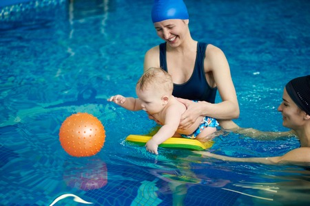 Cute active little child playing in swimming pool. Baby staying on water with board helping and trying getting orange rubber ball in blue water. Family activity and early development concept
