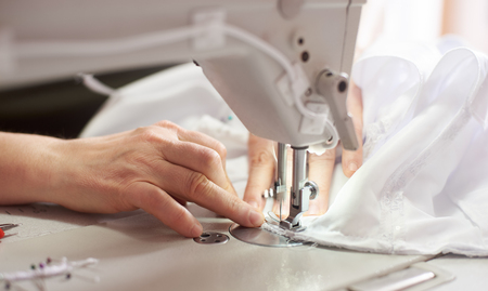 Close up view of sewing process. Female hands stitching white fabric on professional manufacturing machine at workplace. Seamstress hands holding textile for dress production. Light blurred background Reklamní fotografie