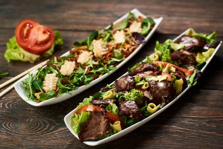 Heiße Salate mit Tintenfisch, Sojasprossen, Rindfleisch, Avocado, Rucola nach Rezept der japanischen Küche in weißer Platte. Essstäbchen, Tomate, Salat, Basilikum auf Holztisch serviert in asiatischer Tradition. Ansicht von oben.
