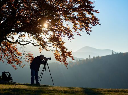 Hiker photographer taking picture of misty mountain landscape using professional camera on tripod on quiet autumn day, standing on grassy valley under large tree with golden leaves under blue sky. Stock Photo