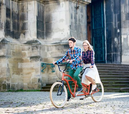Young active happy traveler couple, handsome bearded man and pretty blond woman in glasses riding together tandem bicycle along paved sidewalk on bright sunny summer morning by ancient buildings. Imagens