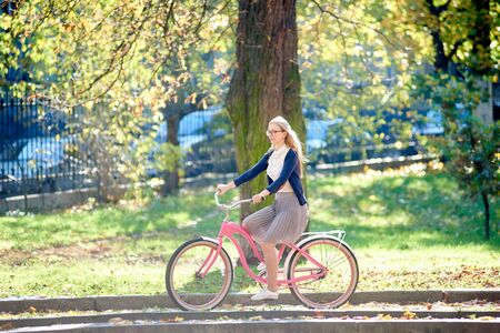 Young attractive smiling blond woman in glasses, white blouse and skirt riding pink lady bike along paved sidewalk in the park on bright sunny autumn day on blurred golden bokeh foliage background. Imagens