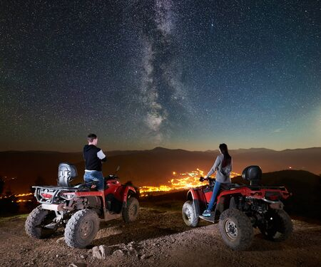 Rear view of happy couple man and woman tourists standing on atv quad motorbikes on the top of mountain, enjoying beautiful view of night sky full of stars, Milky way, luminous village on background